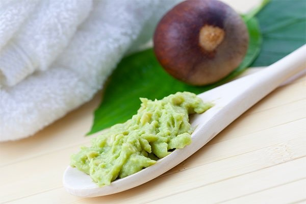 mashed avocado on wooden spoon