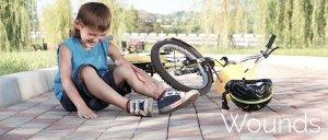 boy with leg wound sitting next to fallen bike and helmet