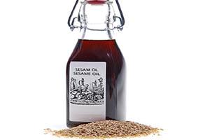 graines de sésame et une bouteille d'huile de sésame