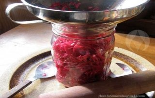 filling jar with red cabbage sauerkraut